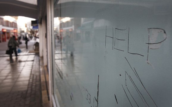 Messages are written on the whitewashed window of a closed retail unit in Manchester