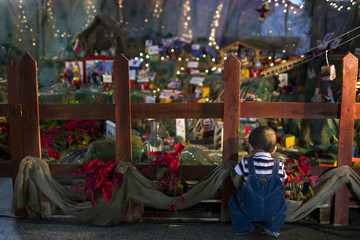 A child looks at a recreation of a Nativity scene with a figurine of Venezuelan President Hugo Chavez in Caracas