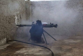 A rebel fighter fires an anti-tank weapon at the Karm al-Tarab frontline