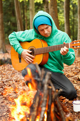 Man playing guitar by campfire