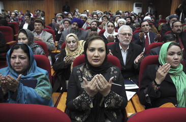 Afghan parliamentarians pray during the opening of the new parliament in Kabul