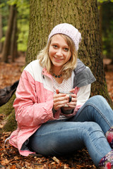 Smiling woman drinking coffee in forest