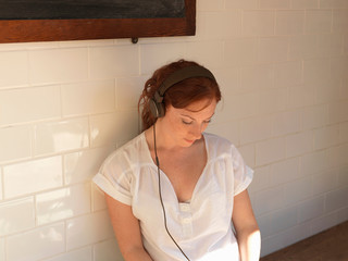 Woman listening to headphones on bench