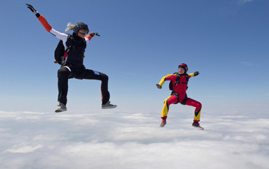 Women skydiving over clouds