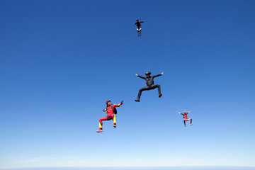 People skydiving over clouds