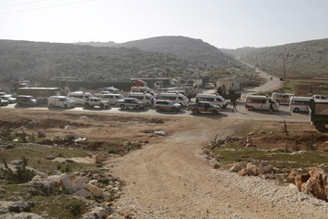 """Fighters from a coalition of rebel groups called """"Jaish al Fatah"""",   escort Syrian Arab Red Crescent ambulances and buses evacuating fighters and civilians from the two besieged Shi'ite towns of al-Foua and Kefraya, in Idlib"""