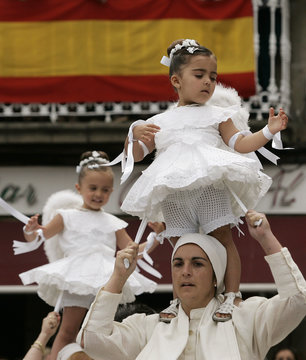 """Women dance with their five-year-old daughters on their shoulders during the """"Coca"""" celebration in Redondela"""