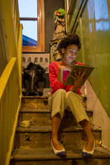 Woman using tablet computer on steps