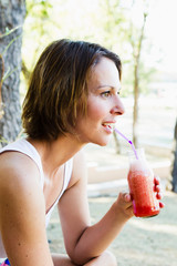 Woman drinking juice outdoors