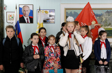 Children wearing red neckerchief attend a ceremony for the inauguration of new members to mark its anniversary, with a portrait of Russian President Vladimir Putin seen in the background, in Stavropol