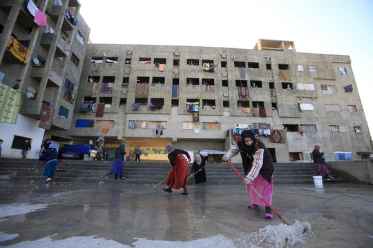 Women clean the floor of a compound housing Syrian refugees in Sidon, southern Lebanon