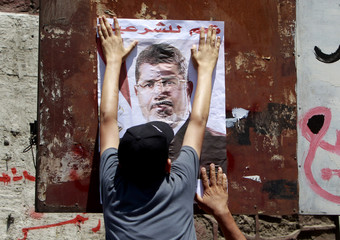 A supporter of deposed Egyptian President Mohamed Mursi hangs a poster of him on a wall during a march from the Al-Fath Mosque to the defence ministry, in Cairo