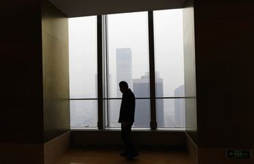 A man stands next to a window of a tall office building on a heavy hazy day in Beijing's central business district