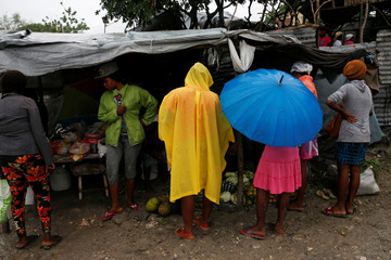 People buy goods on a street at a camp for displaced people while Hurricane Matthew approaches Port-au-Prince
