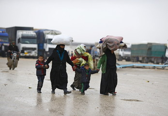 Internally displaced Syrians carry their belongings as they arrive at a refugee camp near the Bab al-Salam crossing, across from Turkey's Kilis province, on the outskirts of the northern border town of Azaz, Syria