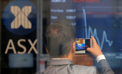 A businessman takes a cellphone picture of Australia's stock exchange index on an electronic board in Sydney