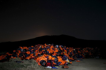 A long exposure photo shows thousands of lifejackets left by migrants and refugees, piled up at a garbage dump site on the Greek island of Lesbos