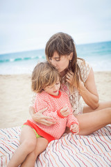 Mother kissing daughter's head on beach