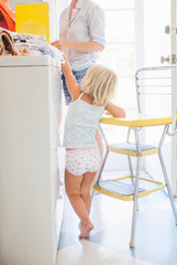 Girl reaching for box of cereal on washing machine