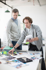 Young man showing plans to colleagues on meeting in creative office