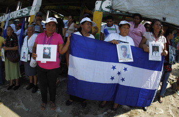 "Women from the ""Caravana de Madres Centroamericanas"" hold a Hondurian flag and photos of missing migrants after arriving at Tecun Uman in a raft"