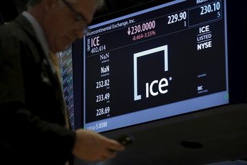 A trader passes by a screen displaying the trading info for Intercontinental Exchange Inc. (ICE) on the floor of the New York Stock Exchange