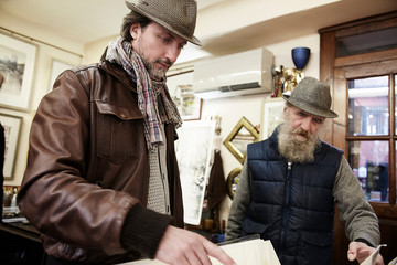 Senior and mid adult man in antique shop