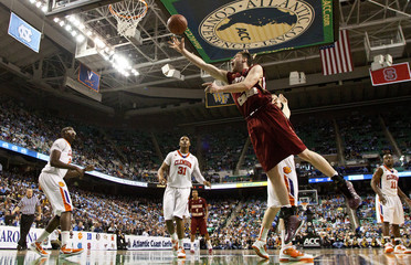 Boston College Eagles forward Joe Trapani shoots around a Clemson Tigers defender during their NCAA men's basketball game at the 2011 ACC Tournament in Greensboro