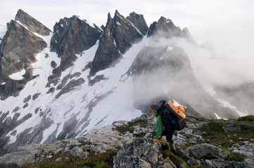 Female backpacker on ridge with fog, Picket Pass, North Cascades National Park, WA, USA