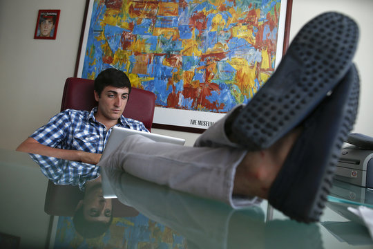 Matteo Achilli looks at a laptop as he sits at the desk in his office in Formello, north of Rome