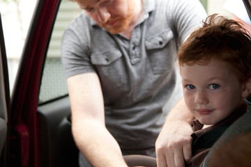 Father securing son in car