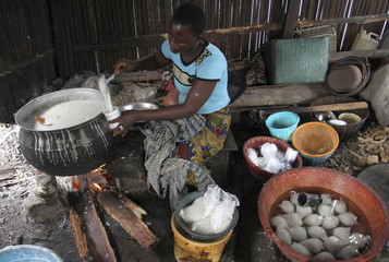 A woman prepares local food in a make-shift kitchen in the Makoko fishing community in Nigeria's commercial capital Lagos