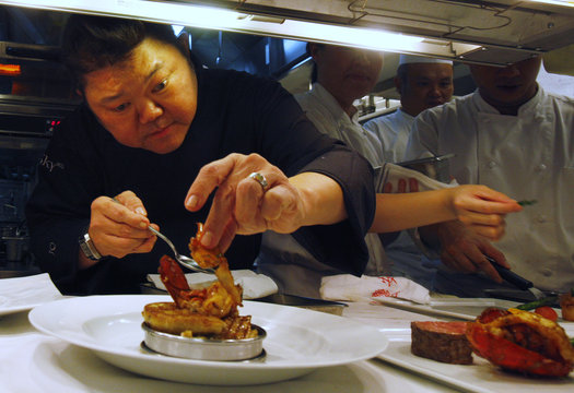 Singaporean chef Justin Quek plates a dish in his kitchen at Sky On 57 restaurant at Marina Bay Sands in Singapore