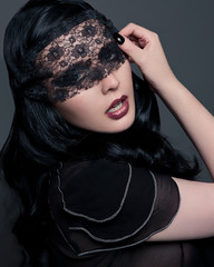 Portrait of young woman with black lace covering eyes