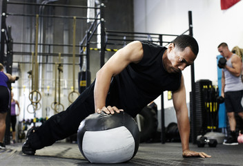 Man doing push up with one hand on medicine ball