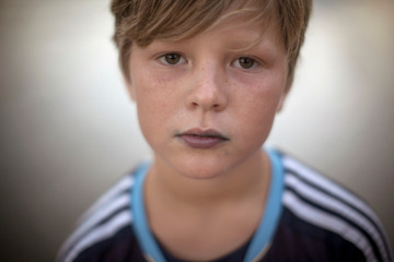 Close up portrait of boy looking at camera with blue stained lips