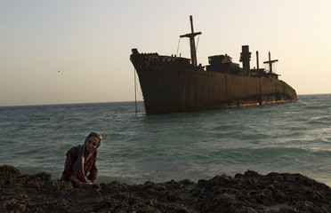 A woman poses for a picture in front of the beached Greek ship Moula F, during sunset off Kish Island, 1,250 km (777 miles) south of Tehran