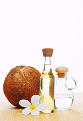 coconut oil and coconuts on green background