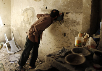 Palestinian man inspects a house, which police said was damaged in Israeli shelling on Thursday that killed two boys and a man from Nutaiz family, in Gaza City