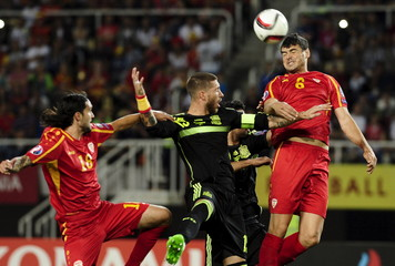 Spain's Ramos jumps for the ball with Macedonians Shikov and Zuta during their Euro 2016 qualification soccer match at Skopje city stadium