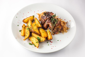 Pork knuckle with potatoes and cabbage on a white plate. Selective focus.