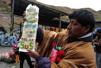 A witch doctor holds candy with images of a frog, a landscape and dollar symbols as part of offerings during celebrations at the Mina Itos, Nueva San Jose in the outskirts of Oruro