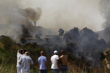 Residents and workers look at a forest fire in Even Sapir