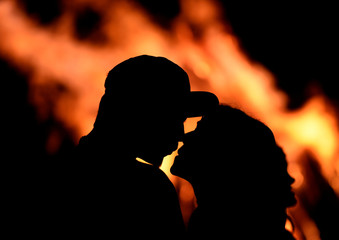 A couple kissing in front of a bonfire during the traditional San Juan's night in Gijon