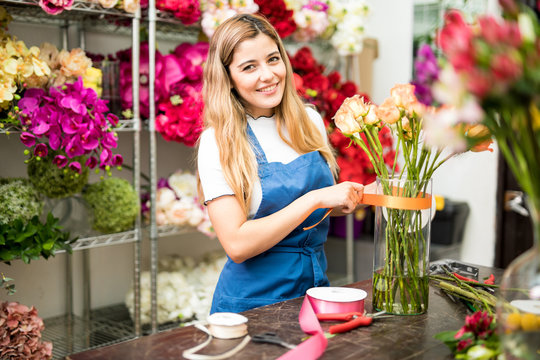 Young florist putting a ribbon on a glass vase