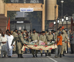Pakistani rangers carry a sick prisoner as he and other prisoners cross into Pakistan following their release from an Indian jail, at Wagah border