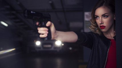 Beautiful brunette sexy spy agent (killer or police) woman in leather jacket and jeans with a gun in her hand running after someone, to catch him on parking