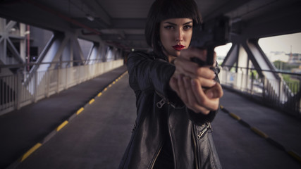 Beautiful brunette sexy spy agent (killer or police) woman in leather jacket and jeans with a gun in her hand running after someone, to catch him on the bridge road