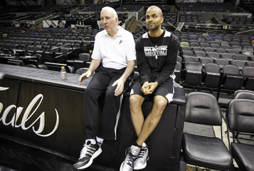 San Antonio Spurs coach Popovich sits with Parker during practice for their NBA Finals basketball playoff series against the Miami Heat in San Antonio