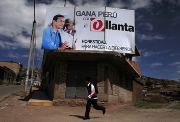 A boy runs in front of Peru's presidential candidate Humala's campaign sign in Poroy town in Cuzco